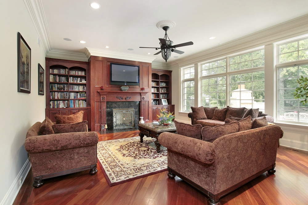 Traditional family room with wood floor, white color scheme and extensive bookshelves on one wall with mounted flat screen TV