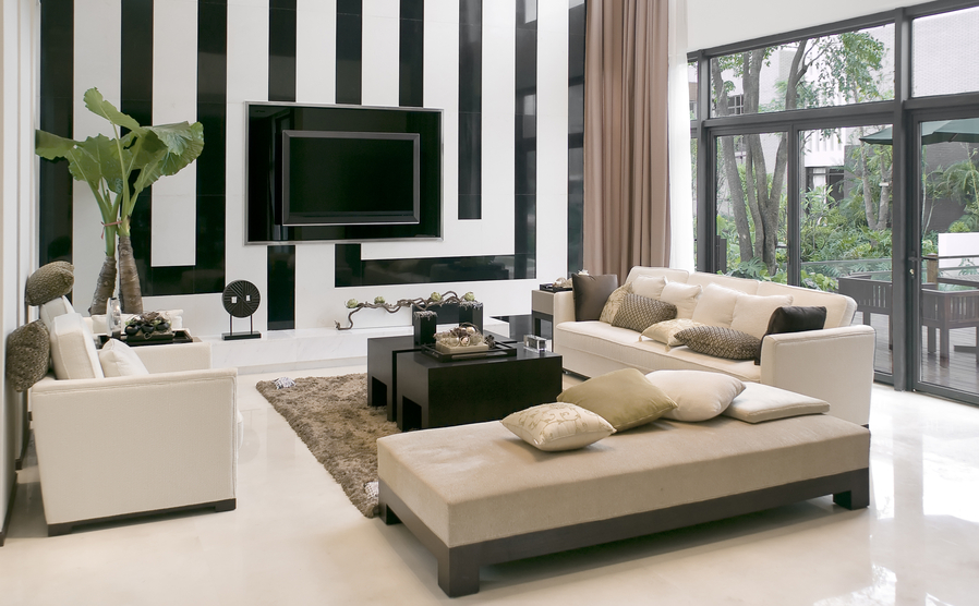 Custom designed family room with black and white patterned wall, floor-to-ceiling windows and light-colored furniture on white floor with a rug