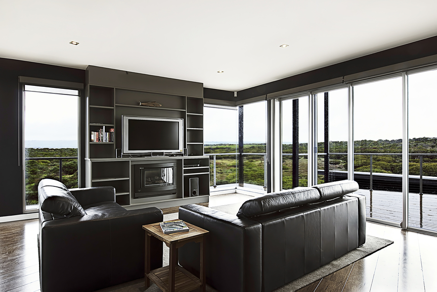 Modern family room style with white ceiling wood floor, dark leather furniture, floor-to-ceiling windows and mounted flat screen television