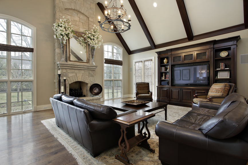 spacious family room in luxury home with cathedral ceiling exposed wood beams dark leather