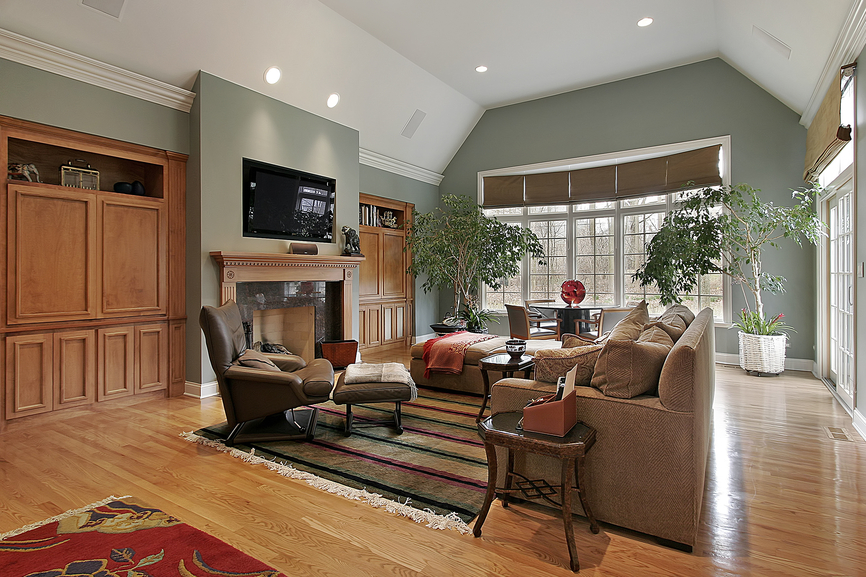 Casual family TV room with wood floor, white ceiling, green walls, throw rug and television mounted above the fireplace