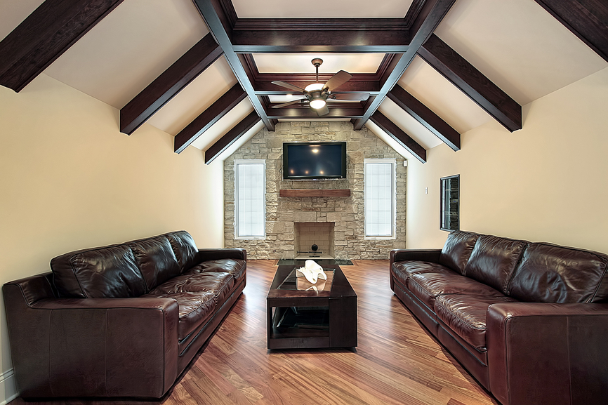 Loft family room with wood flooring, exposed dark wood ceiling beams, 2 dark brown leather sofas, brick fireplace with mounted flat screen TV above