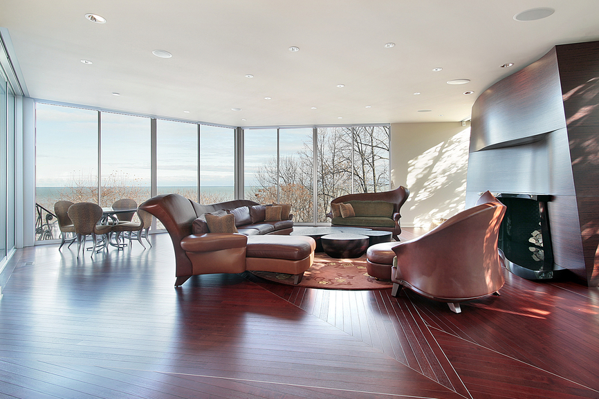 Modern open concept living room/family room combination with leather chairs, red wood flooring, white ceiling and floor-to-ceiling windows surrounding the space