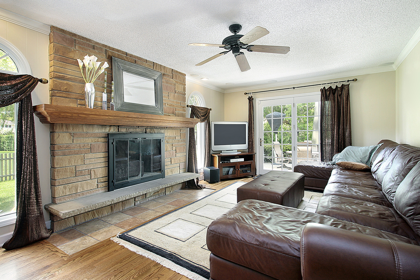 Separate family room with brick fireplace, white ceiling, wood floors and large brown leather sofa with ottoman. TV situated in the corner of the room.