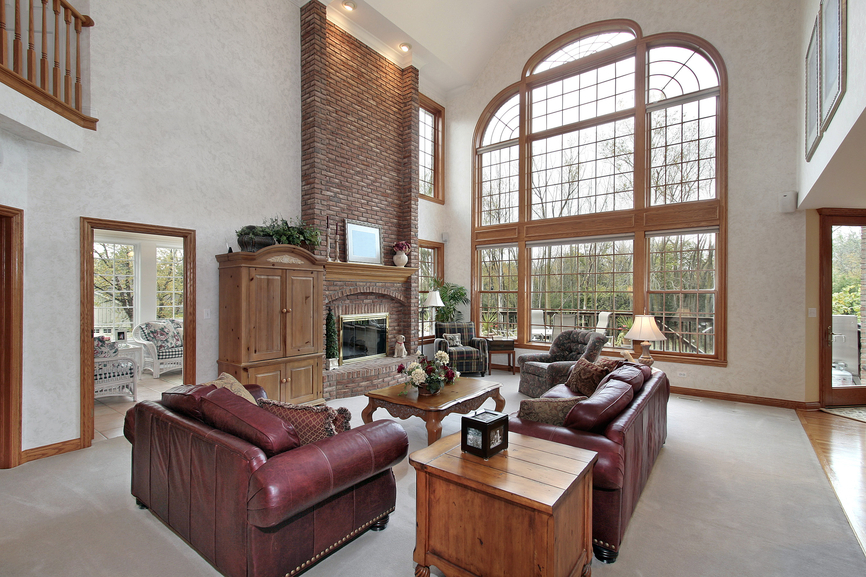 Great room family lounge with large 2-story arched window, brick fireplace, carpet flooring and red leather furniture