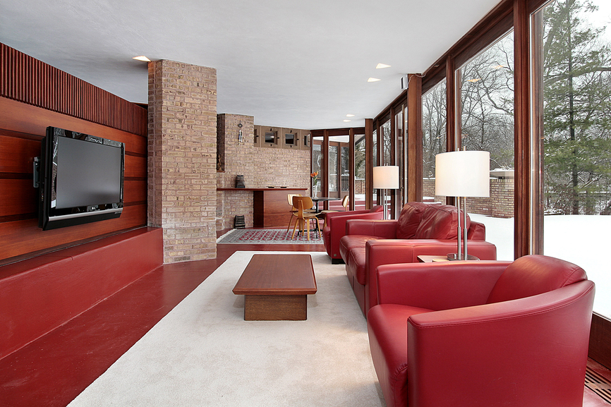 Modern family room style with red and brick walls and furniture on white rug with floor-to-ceiling windows.
