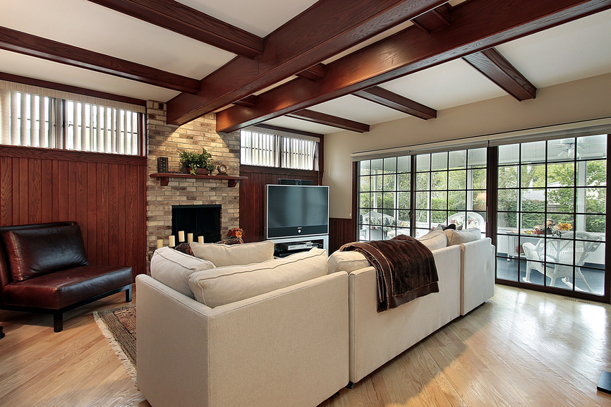 Family room with extensive use of wood showcasing exposed ceiling beams, wood floor, wood walls offset with white sectional sofa