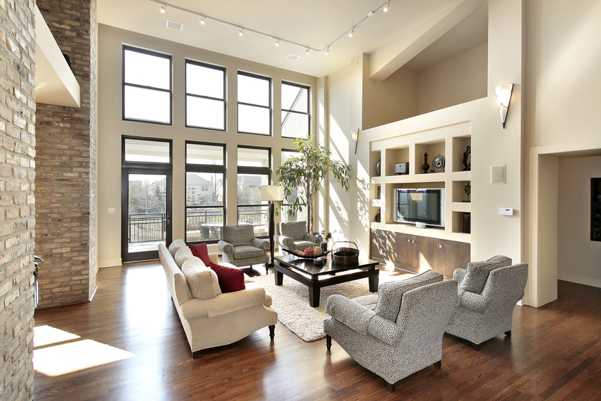 light colored family room with elevated ceiling large framed windows