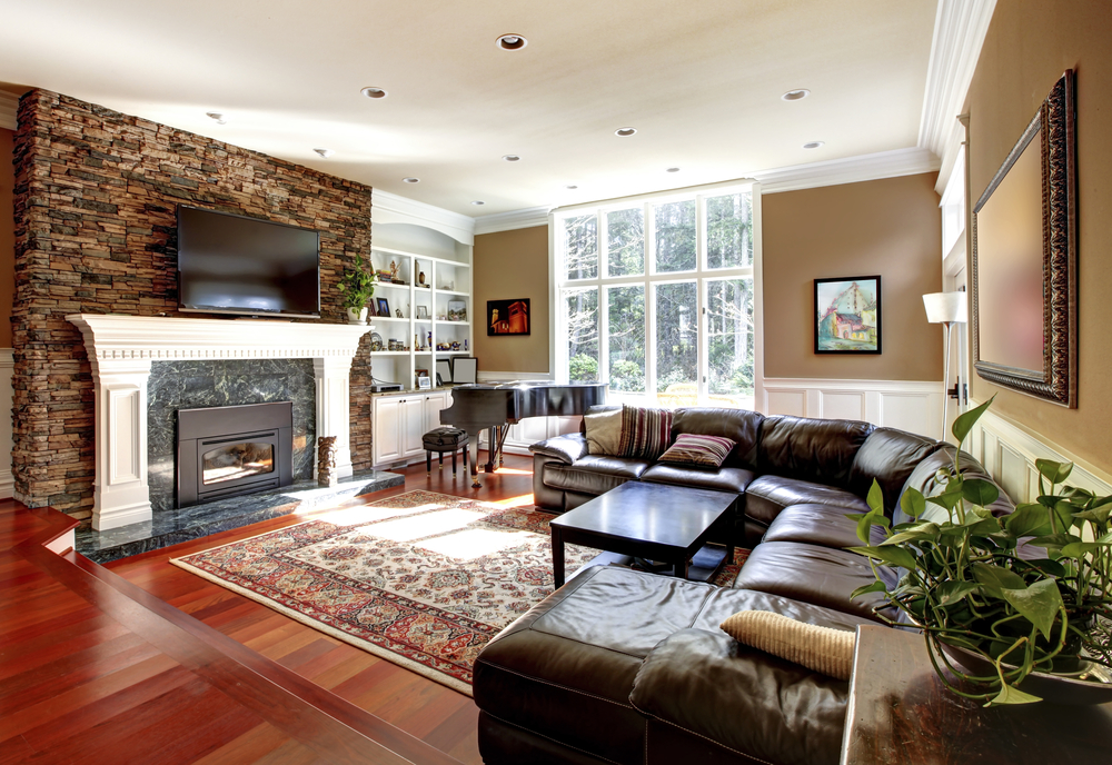 Family entertainment room with L-shaped curved leather sofa, glass coffee table, wood flooring, beige walls, white ceiling, white fireplace mantle with TV mounted against the brick fireplace wall