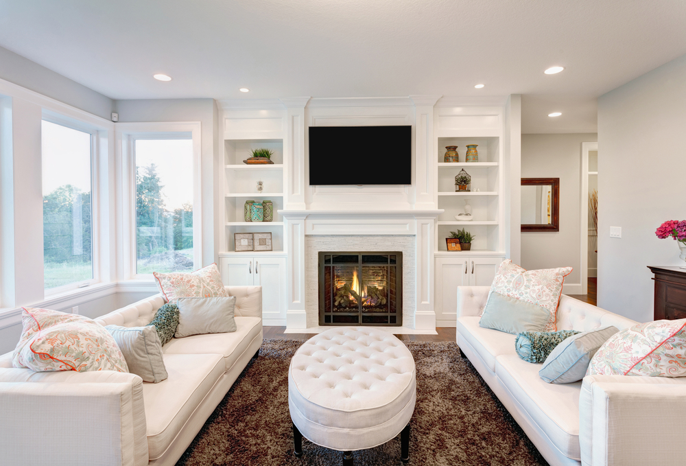 All white family room with built-in white shelving around fireplace with two white sofas