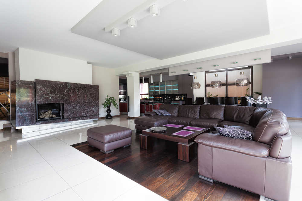 Large open family room on wood floor wrapped with white tile floor. Furniture includes large L-shaped curved leather sofa, wood coffee table and matching ottoman