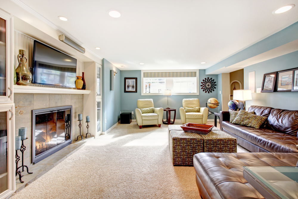 Long family room with long leather sofa spanning much of the room and two reading chairs at the end with flat screen television mounted above the fireplace