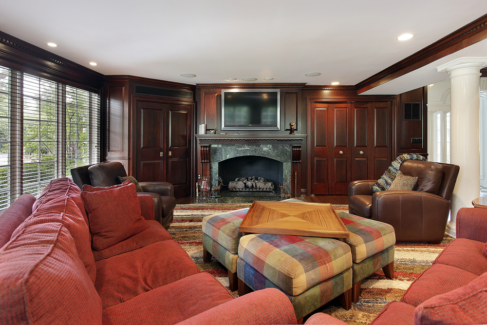 Dark wood paneled family room with red furniture situated on large rug facing stone fireplace with TV mounted above