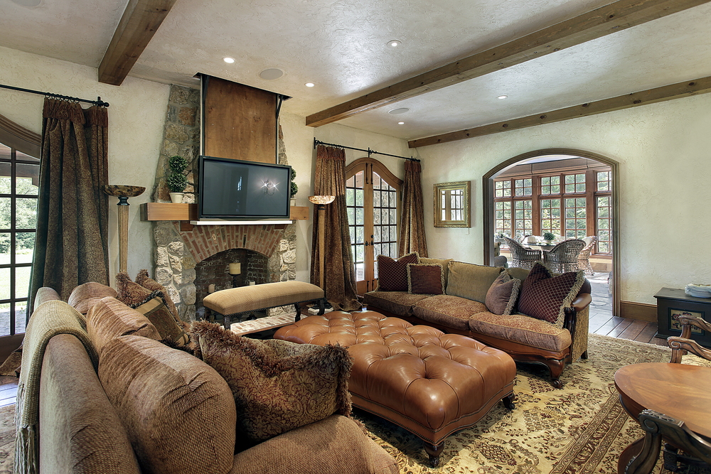 masculine family room design with oversized sofas large leather ottoman exposed wood ceiling beams