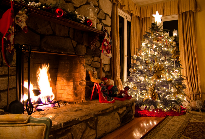 Traditional fireplace with rock surround, set against a Christmas tree backdrop.