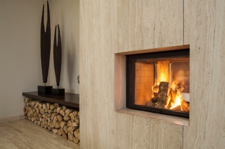 Travertine fireplace with stacked wood to the side