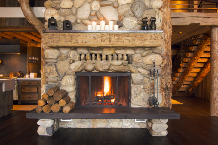 Rock fireplace surround with rough wooden mantel