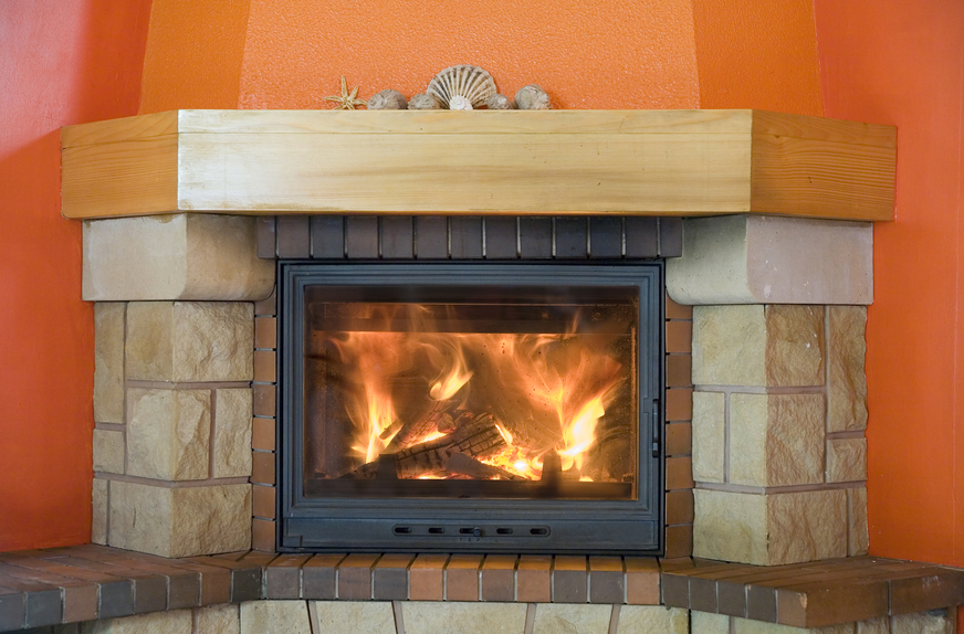 Solid looking fireplace with orange walls