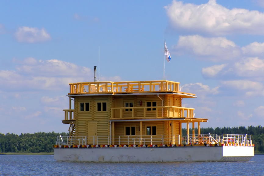Two-story floating log home on large barge