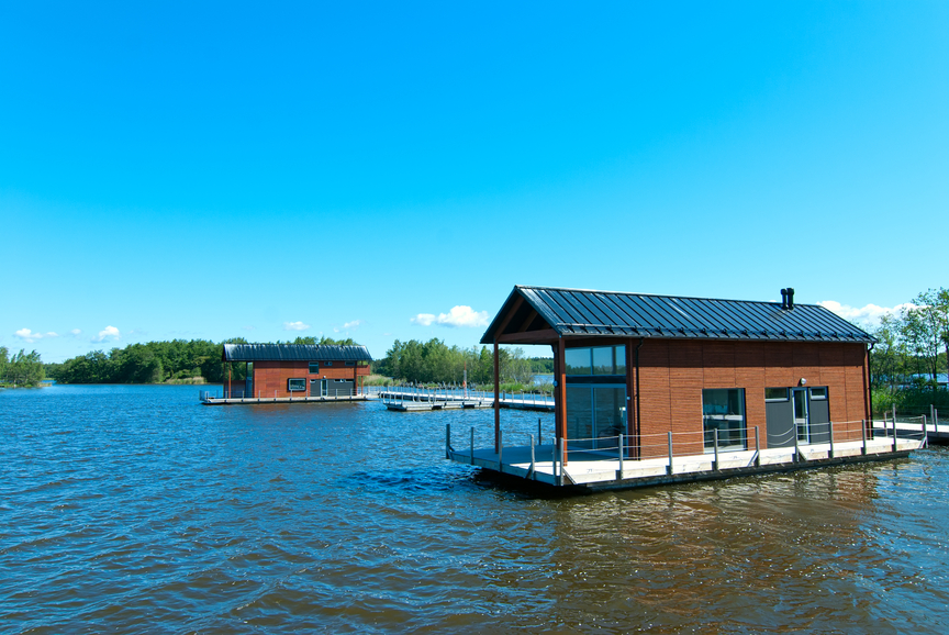 Small floating home with wrap-around deck that doubles as a boat dock
