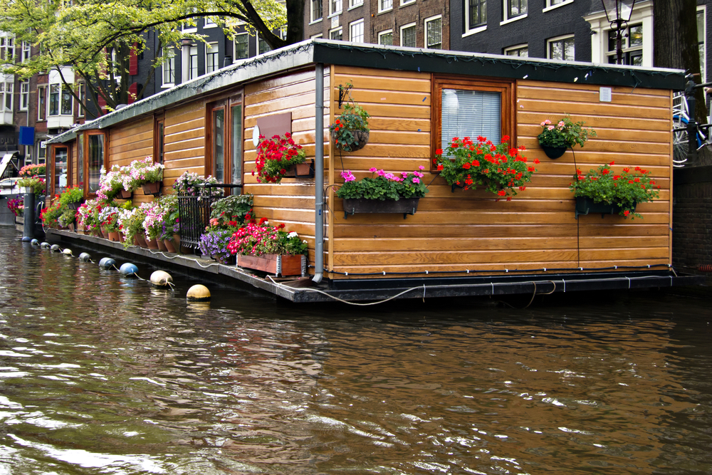 One-story floating canal boat home with wood exterior
