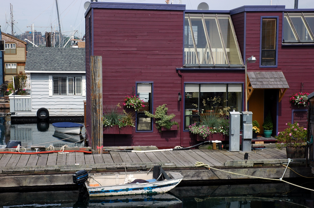Close-up of purple 2-story floating home with dock and large sloping skylight