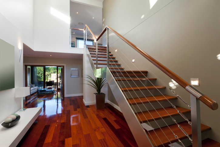 Two-story modern home entrance foyer with wood floor and straight wood and metal staircase