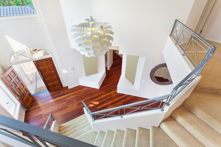 2-story foyer with hard wood floor, white walls and single-winderwhite  staircase