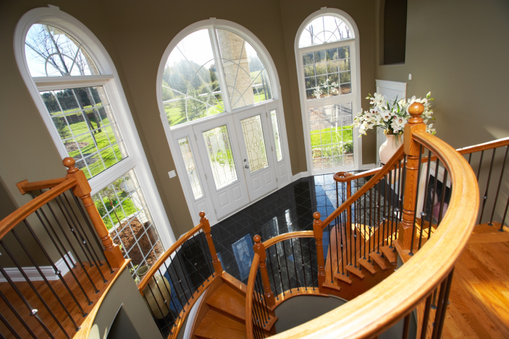 2-story foyer with black floor, brown walls, wood spiral stairs and white front door
