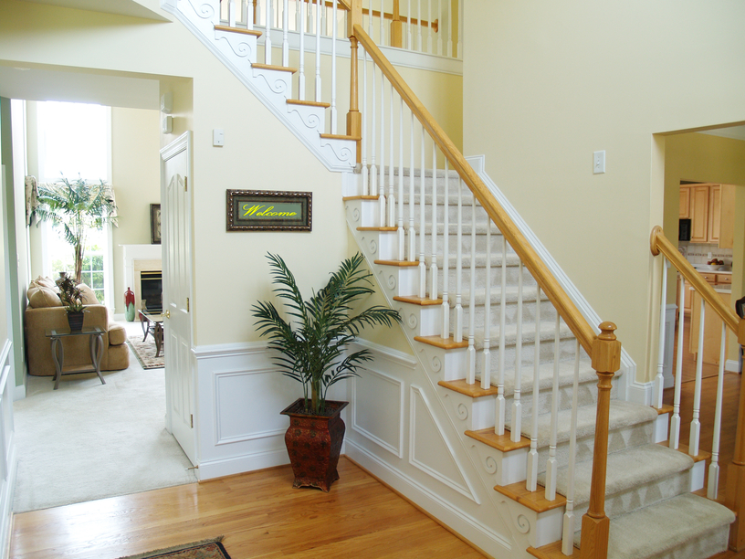 Small foyer with single-winder stairs and light wood flooring