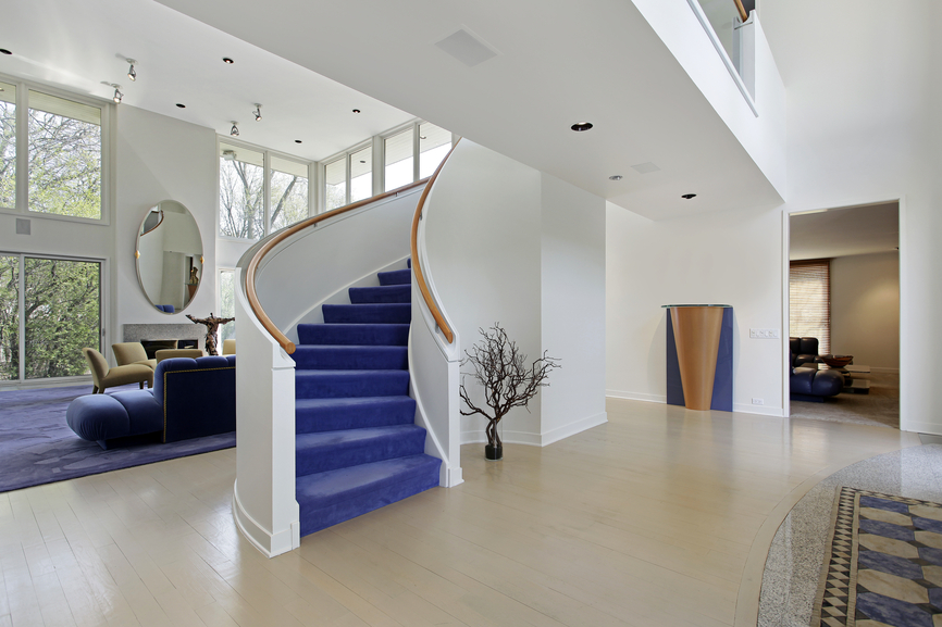 White walled foyer with blue staircase opening up into 2-story living room