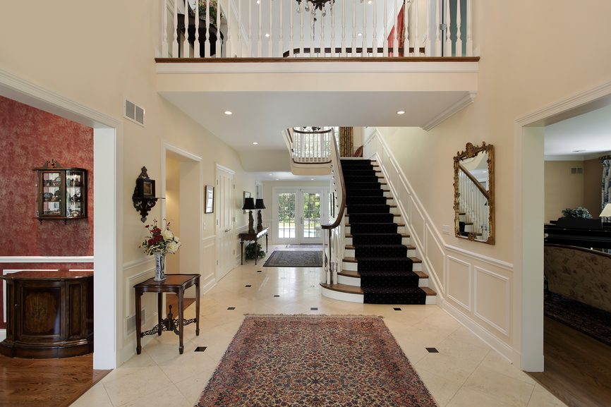 White marble foyer with rug and straight staircase with view of landing
