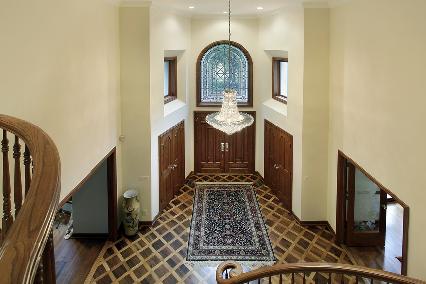 Foyer with diamond pattern wood flooring with rug