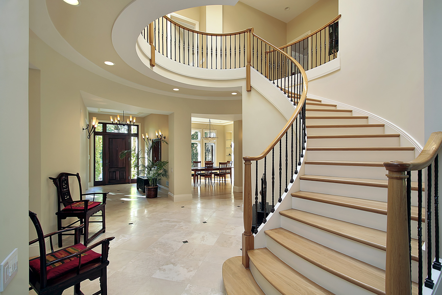 Marble-floor foyer in luxury home with arched stairs