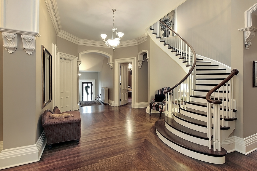 One-story hard wood floor entry hall with dark wood and white arched staircase