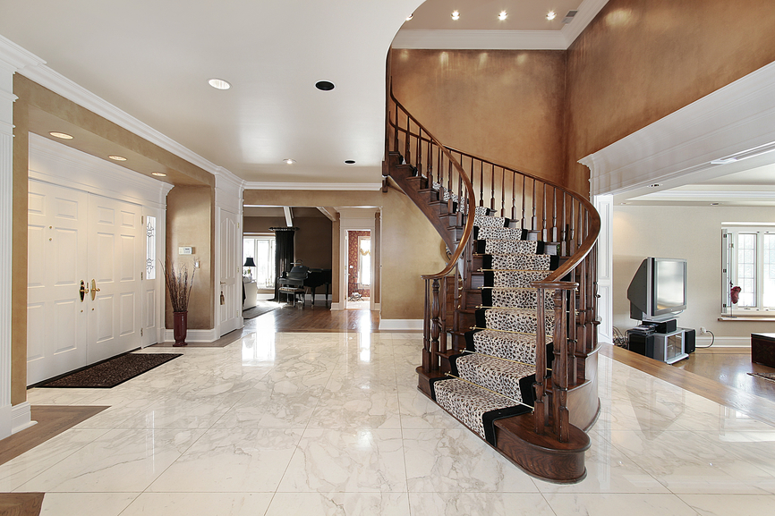 one-story foyer with marble floor and arched wooden stairs with carpet runner