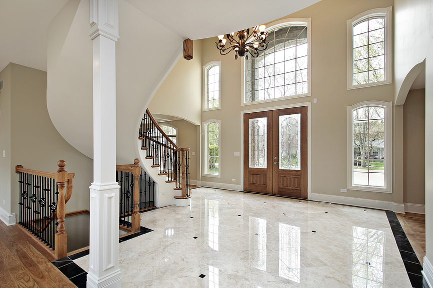wood and marble floor foyer with arched staircase plenty of window rising up two stories