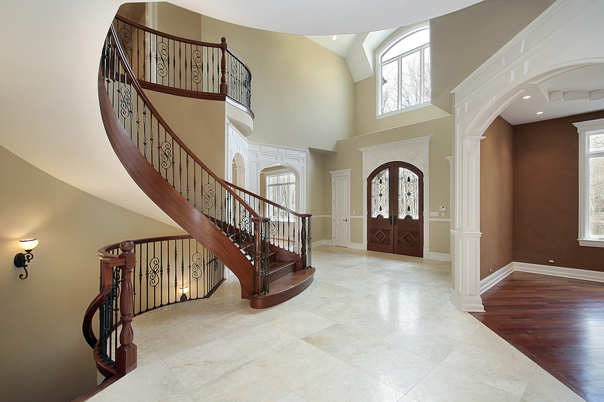 Expansive two-story foyer with arched wooden staircase