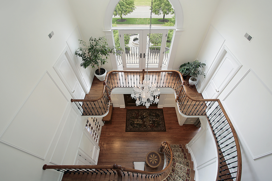 View of 2-story entrance foyer from landing with arched staircase
