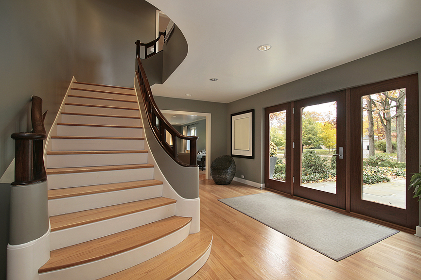 Contemporary foyer with light wood floor and straight stairs leading to landing.