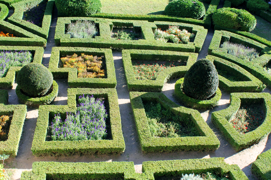 Close-up aerial picture of a section of extensive English Garden containing maze-like hedge sculptures and sculpted trees