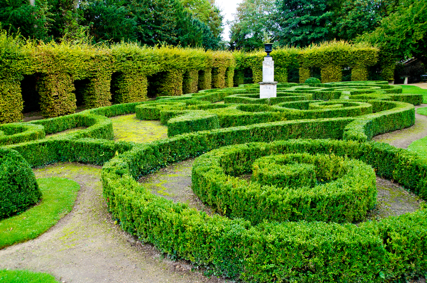 Short hedge maze surrounded by pillar-sculpted hedge