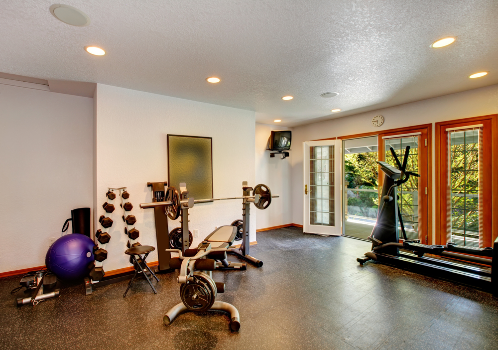 home gym lighting. large exercise space with dumbbells and cardio machine doors to the outside home gym lighting