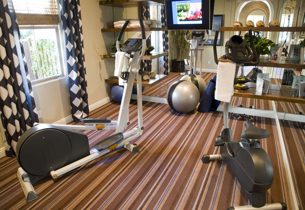 Home gym with cardio machines and television mounted on mirrored wall