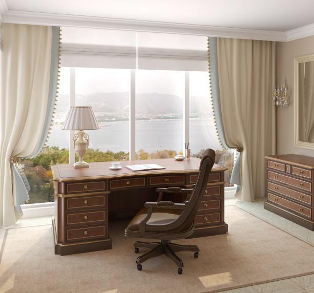 Large office in luxury home with large wood desk in front of floor-to-ceiling window covered with drapes