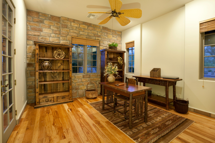 Mid-sized home office with rustic wood flooring, brick wall, wood office furniture entered into via french doors