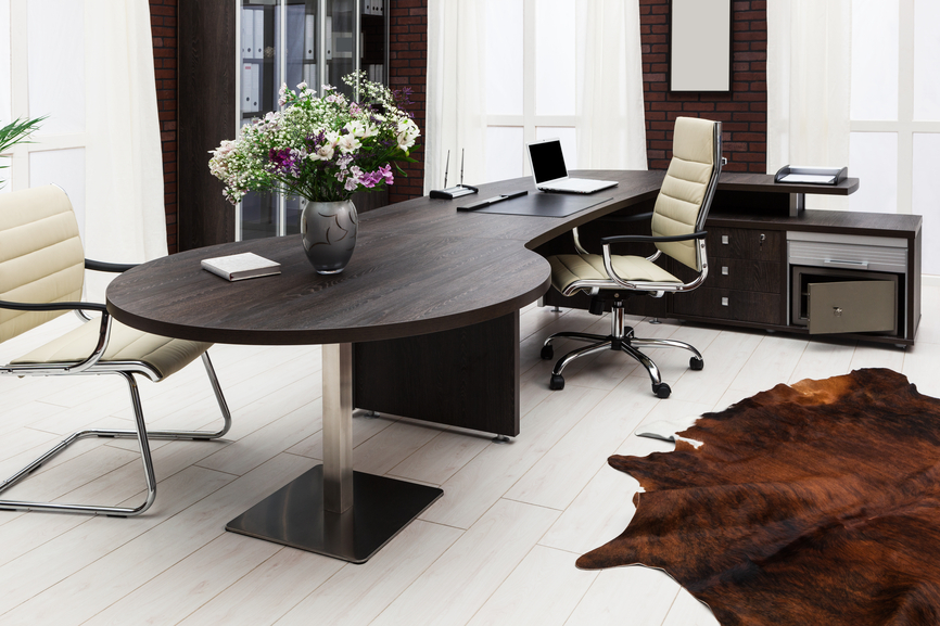 modern home office with light wood floor and dark wood desk with cream  colored office furniture.