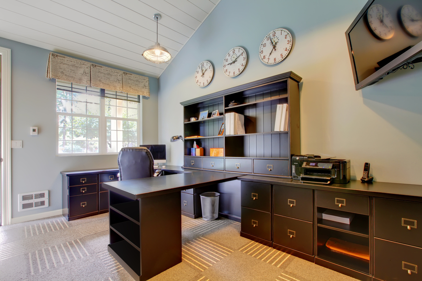Home office with U-shaped desk and work station. Multiple clocks on the wall to display the time of multiple time-zones