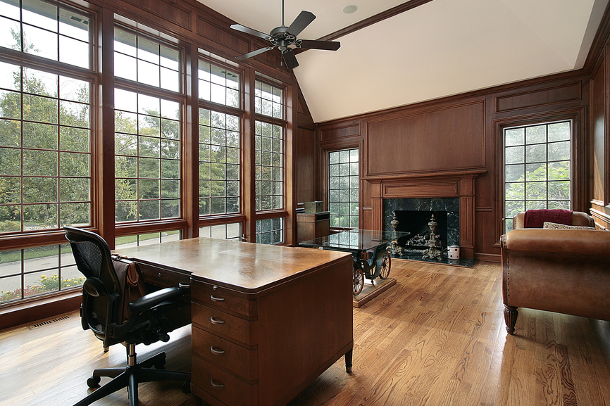 Large wood paneled office in luxury home with wood desk, rolling black leather chair, sitting area with brown leather furniture in front of fireplace