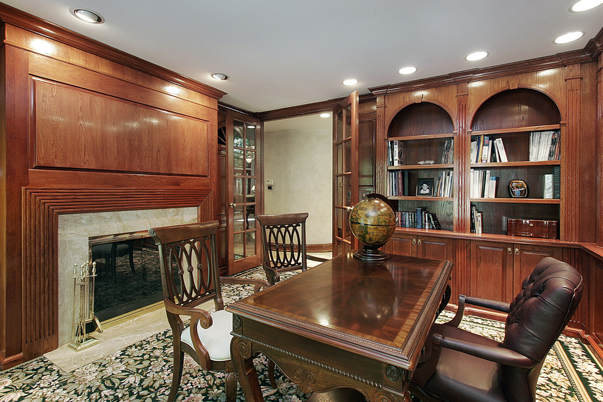 ... bookshelves, ornate wood desk with brown leather chair and fireplace